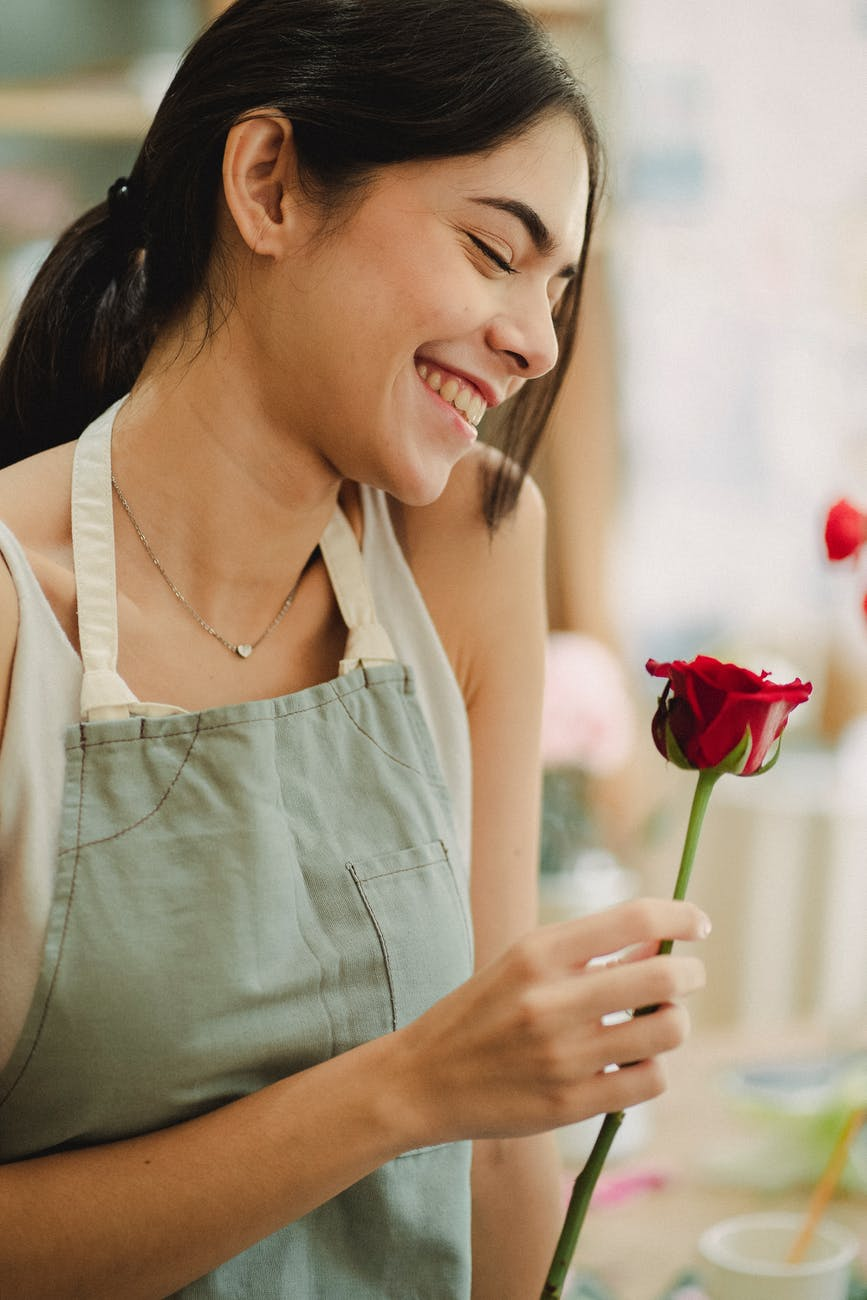 romantic female standing with red rose in hand