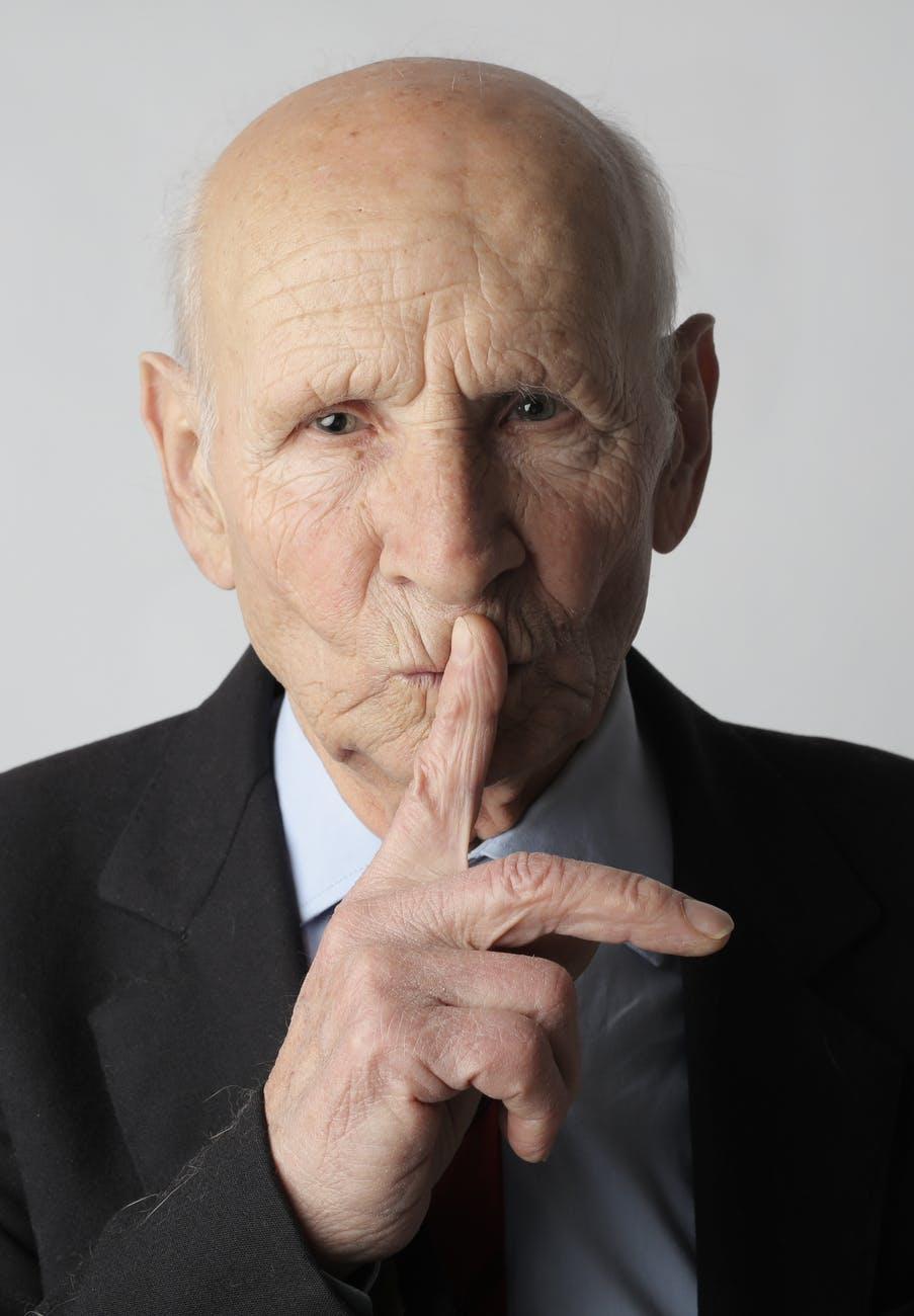 elderly gentleman making silence gesture in studio