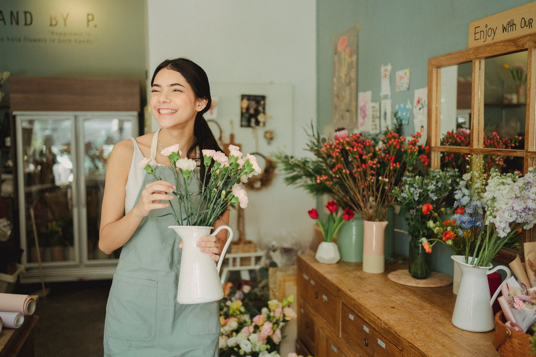 happy florist standing with vase of flowers