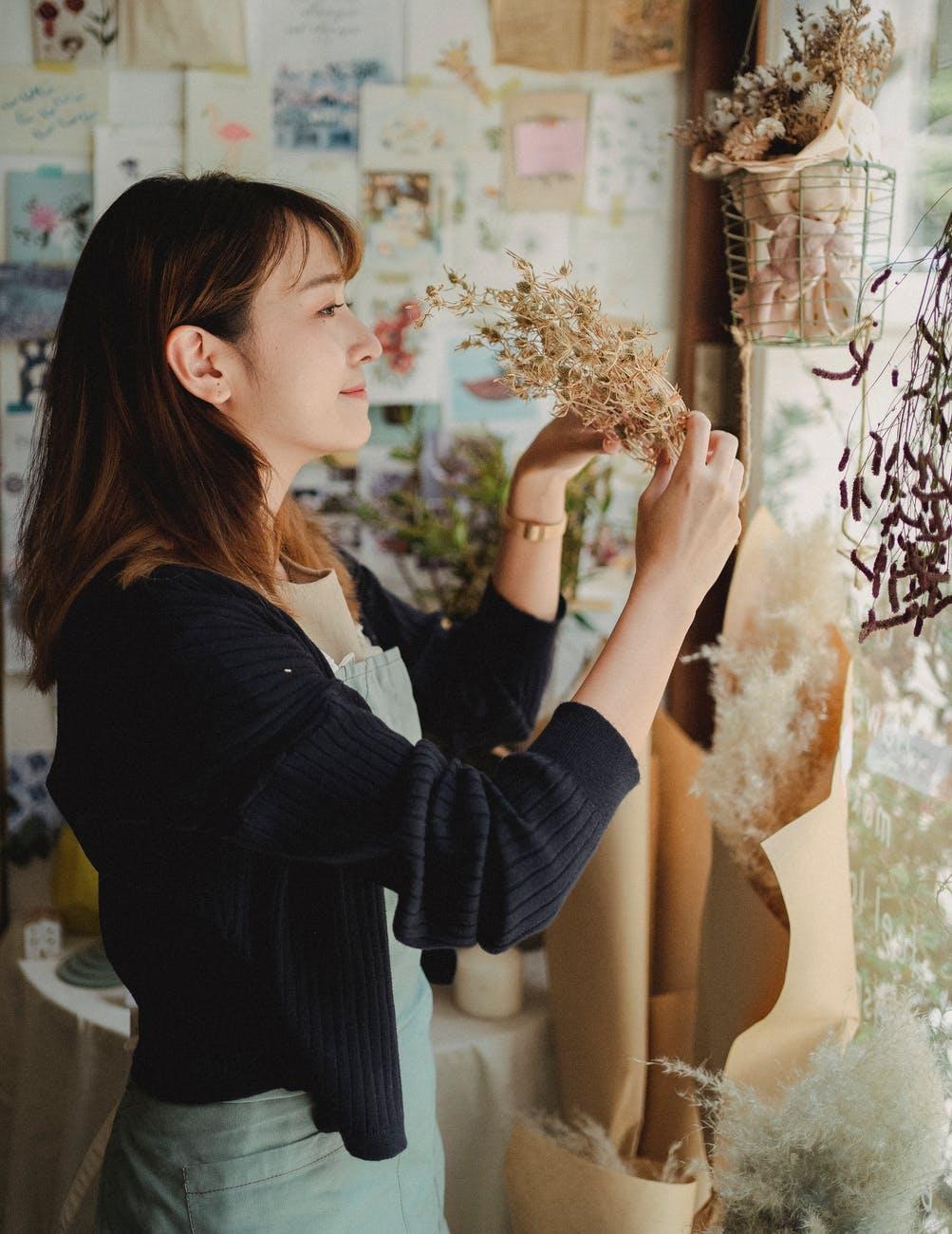 calm asian female choosing herbarium in store