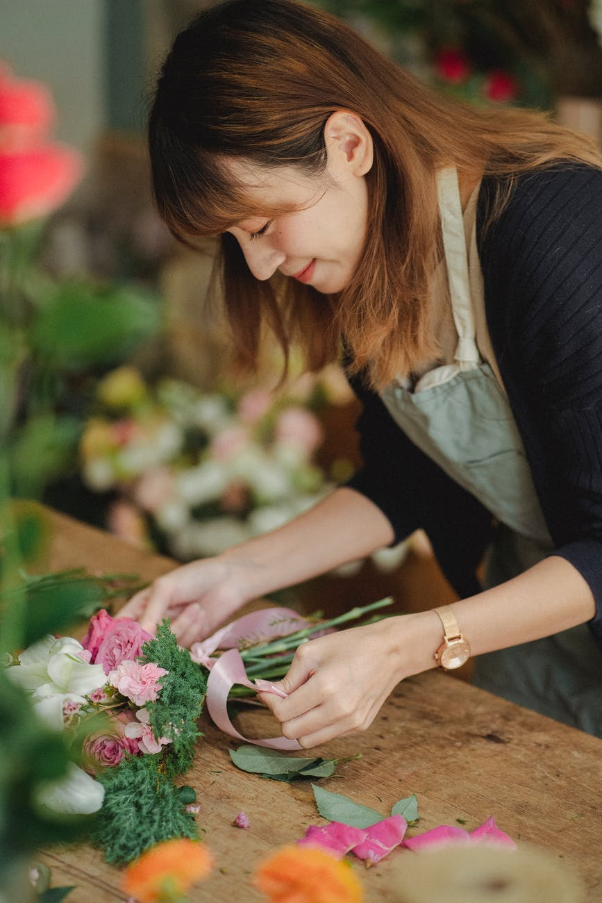 cheerful florist making bouquets in shop